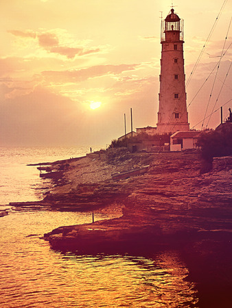 Lighthouse at sea coastline. Sunset on beach. Tined toned coloration image with gold color filters. Stock Photo