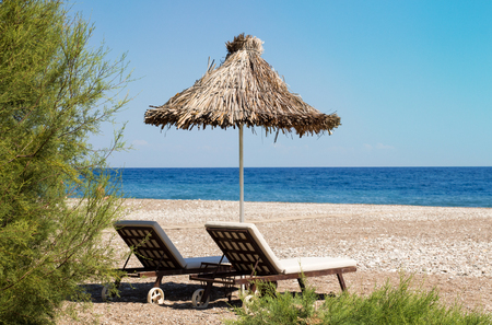 Sunshades and chaise lounges on beach. Summer seascape. Selective focus Stock Photo