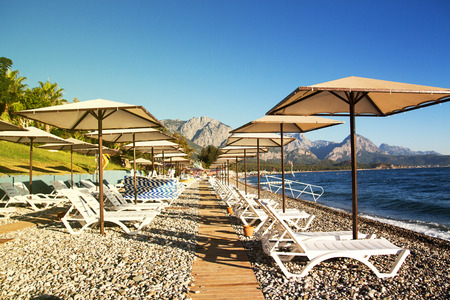 Sunshades and chaise lounges on beach. Turkey, Kemer. Beautiful view of mountains and sea Stock Photo