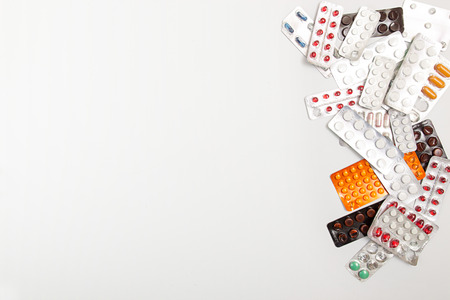 heap: Heap of medicine tablets and pills in blisters on white background. Copy space. Healthcare or medicament addiction concept