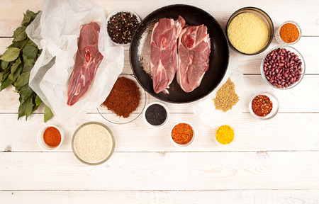 Chopped raw lamb steaks on parchment on board. Ingredient for preparing dinner on white wooden table. High angle. View from above Stock Photo