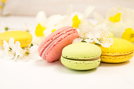 Green, yellow, pink macarons on white background against of narcissus and cherry blossom Stock Photo