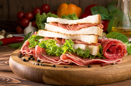 Sandwich with salami. Lettuce, cherry tomatoes, mustard, basil, garlic on wooden background. Rustic stale. Close up