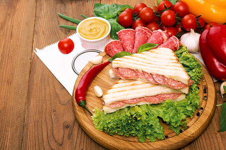 Sandwich with salami. Lettuce, cherry tomatoes, mustard, basil, garlic on wooden background. Rustic stale.