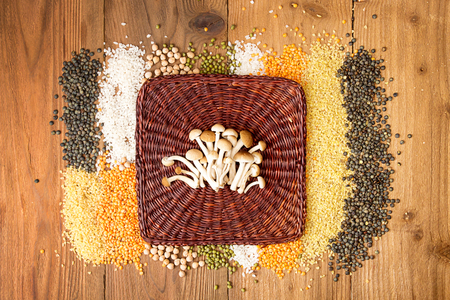 mung: Collection raw cereal beens on wooden background. Couscous, yellow and green lentils, mung beans, chickpeas, rice and honey mushrooms honey fungus honey agarics edible mushrooms. Flat lay pop art still life. Top view