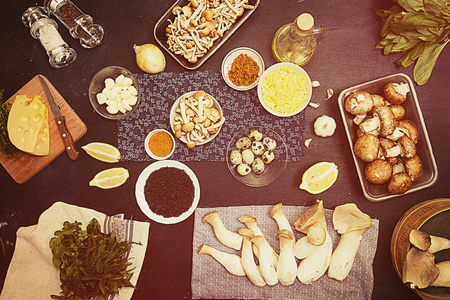 quail: Group of raw ingredients for preparing vegetarian dinner.Oyster mushrooms king mushrooms and vegetables on dark background. Oyster mushrooms king mushrooms eryngii, champignons, honey mushrooms, eggplants, arugula, black sesame, lemon. Healthy food concep