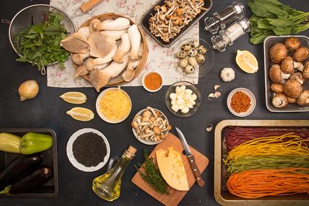 Group of raw ingredients for preparing vegetarian dinner.Oyster mushrooms king mushrooms and vegetables on dark background. Oyster mushrooms king mushrooms eryngii, champignons, honey mushrooms, tagliatelle, eggplants, arugula, black sesame, lemon. Health