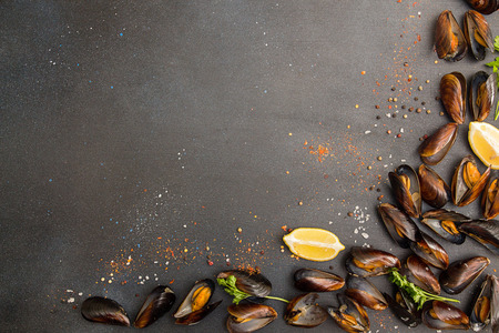 Overhead of row of frilled mussels with lemon and parsley. Healthy food concept. Copy space. Top view