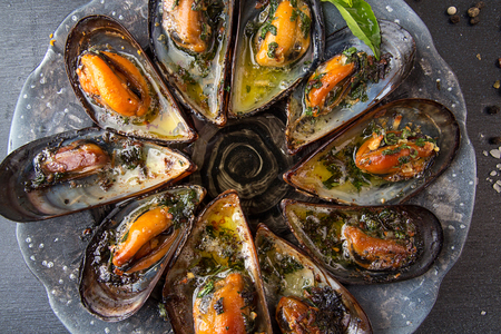 Mussels baked with butter and parsley in shell mussels. Lemon, parsley and spices around plate on dark background. Top view. Healthy eating concept