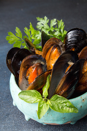 Mussels baked with butter and parsley in blue ceramic bowl and sauce bowl on dark background background. Copy space Фото со стока