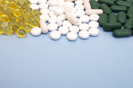 Pills background. Heap of assorted various medicine tablets and pills in blisters different colors on blue background. Healthcare or medicament addiction concept. Copy space. Top view