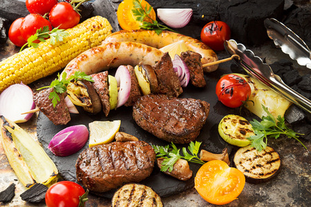 Assorted delicious grilled barbecue meat with vegetable. Beef grilled steaks with spicy sausages, beef kebabs, corn, cherry tomato,  pepper, slices of onion, zucchini, eggplant. Picnic bbq party concept