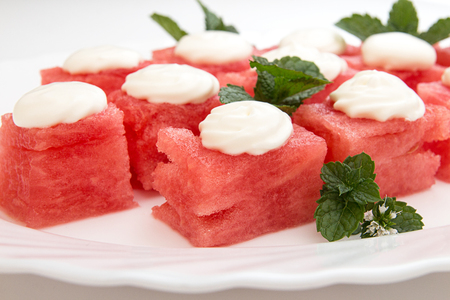 Slices of watermelon with vhipped cream scoops on top. Sweet summer dessert on white plate. Close up. Vegeterian dieting healthy eating. Stock Photo
