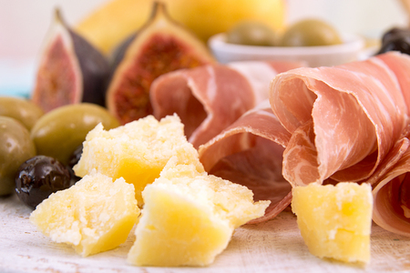 Slices of prosciutto, pieces of cheese, olives and figs on background