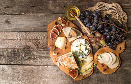 cheese plate with  pieces moldy cheese, prosciutto, pickled plums, olives, grapes, figs, honey, pear,  walnuts, almonds, cashews on old wooden background. Rustic style. Top view. Copy space. Stock Photo