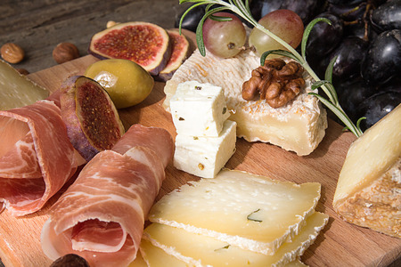 Set of pieces moldy cheese, prosciutto, pickled plums, olives, grapes, figs, honey, pear, walnuts, almonds, cashews on old wooden background. Rustic style. Foto de archivo