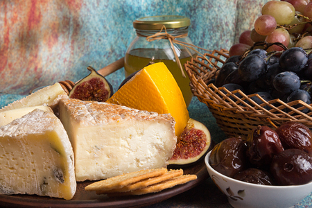 Food composition with blocks of moldy cheese, pickled plums, grape bunch, crackers, figs on blue red background.