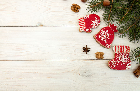 Overhead of Christmas New Year holiday background. Red gingerbread cookies boots, meetens, bag with gift, fir branch tree on white wooden background. Top view. Copy space