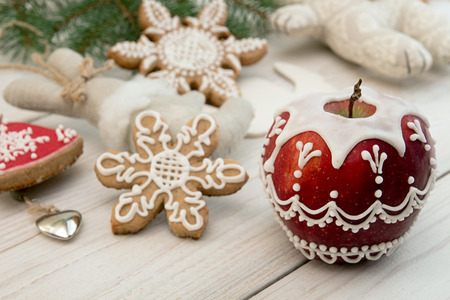 Christmas New Year decoration. Painted red apple with sugar icing, gingerbread cookies.