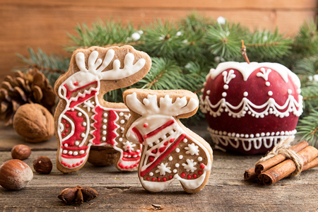 Gingerbread cookies elk and deer, painted apple, fir tree branch. Christmas New Year holiday decor. Stock Photo