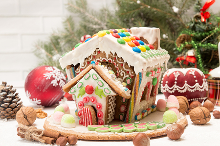 Gingerbread house. Christmas holiday sweets. European Christmas holiday traditions. Christmas gingerbread house and holiday decorations. Copy space. Stock Photo