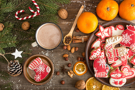 Overhead of Christmas New Year holiday background with gingerbread cookies, fir tree branch, mandarins, cocoa drink over on old  wooden table. Top view.