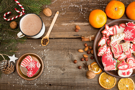 Overhead of Christmas New Year holiday background with gingerbread cookies, fir tree branch, mandarins, cocoa drink over on old  wooden table. Top view. Copy space. 写真素材