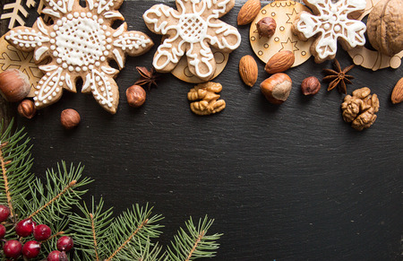 Overhead of Christmas New Year holiday background. Greeting card with red gingerbread cookies and fir branch tree on black slate background. Top view. Copy space