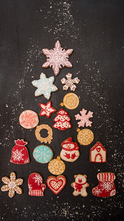 Overhead of Christmas New Year holiday. Greeting card with gingerbread cookies in shape fir tree on black. Top view. Copy space Foto de archivo