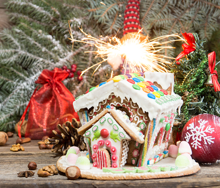 Gingerbread house. Christmas holiday sweets. European Christmas holiday traditions. Christmas gingerbread house, sparkler, Bengal light and holiday decorations. Copy space.