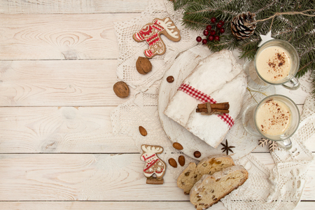 Traditional Christmas dresden cake stollen with candied fruits and almonds, glasses eggnog. Christmas New Year decoration.Top view. Copy space. Foto de archivo