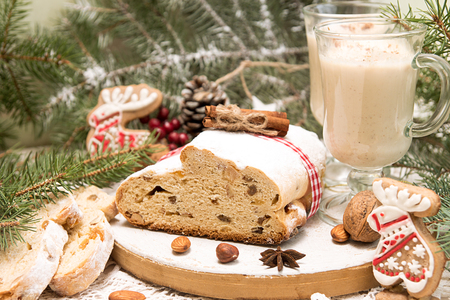 Traditional Christmas dresden cake stollen with candied fruits and almonds, glasses eggnog. Christmas New Year decoration.