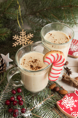 Eggnog,winter Christmas traditional hot drink with milk, eggs, rum. Christmass New Year decoration with gingerbread cookies.