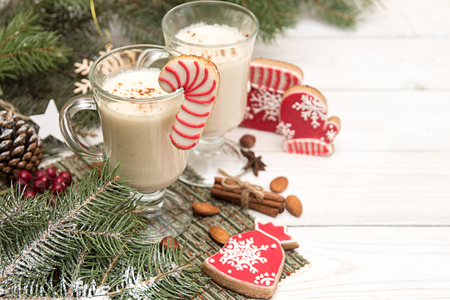 Eggnog,winter Christmas traditional hot drink with milk, eggs, rum. Christmass New Year decoration with gingerbread cookies. Top view. Copy space. 写真素材