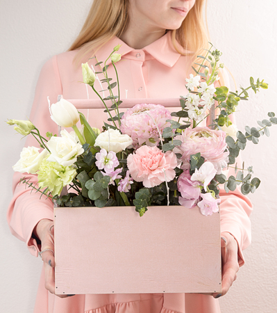 Flowers for Happy Easter. Pink wooden box with flowers roses and carnations in girls hands on white background Foto de archivo