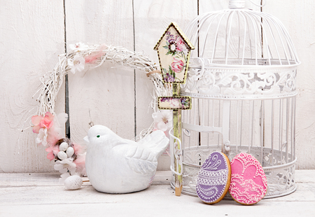 Happy Easter decoration for greeting card. Wooden bird, birdhouse, gingerbread Easter cookies in shape of Easter eggs on white background. Vintage style.