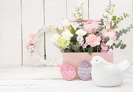 Happy Easter decoration for greeting card. Wooden bird, gingerbread Easter cookies in shape of Easter eggs and basket with flowers on white background. Vintage style. Copy space.