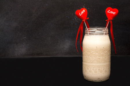 Two valentines in glass jar with milk cocktail on black background. Valentine day romantic love concept. Copy space.  Foto de archivo