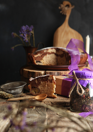 Banana cake bread traditional pie on rustic wooden surfase and black background. Trend purple color decor. Front view. Dark style.