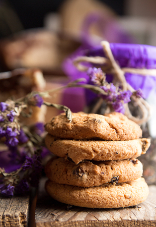 Oat cookies with raising and chocolate on purple flowers background. Rustic style. Healthy food concept.