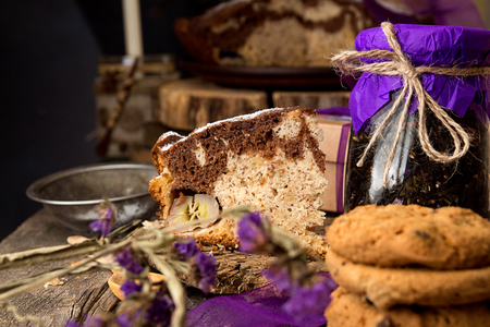 Banana cake bread traditional pie on rustic wooden surfase and black background. Trend purple color decor. Front view. 写真素材