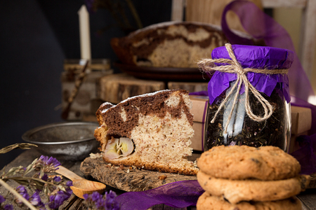 Banana cake bread traditional pie on rustic wooden surfase and black background. Trend purple color decor. Front view. Foto de archivo