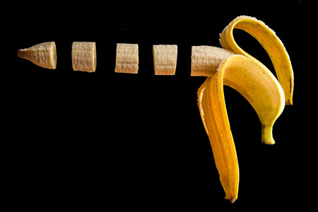 Banana onblack background. Part of banana in gun shape. Isolated. Copy space. Foto de archivo