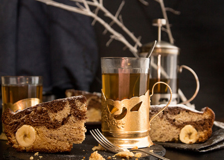 Banana cake bread traditional pie and green tea glasses in vintage retro glass-holder on black background. Front view. Dark style.