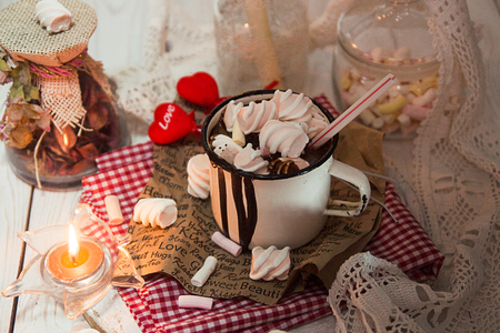 Mug of hot chocolate drink with marshmallow candies on top and candles on white background. Valentins day love concept. Top view.