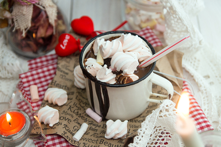 Mug of hot chocolate drink with marshmallow candies on top and candles on white background. Valentins day love concept.