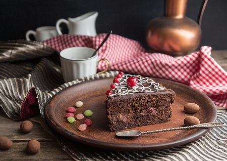 Piece of chocolate cake on plate on old wooden background.