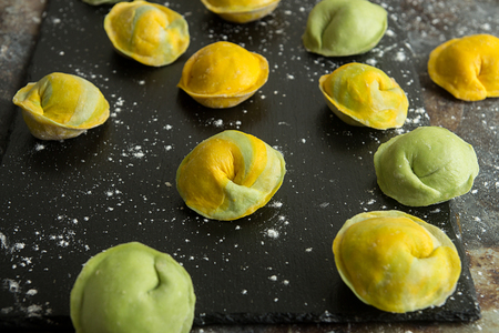 Homemade raw dumpling, yellow and green colors, traditional East European food before boiling. Top view. Stockfoto
