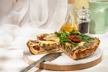 French opened pie quiche with tuna  chicken, broccoli, spinach, pepper, eggs, cheese and dried tomato on white wooden background.