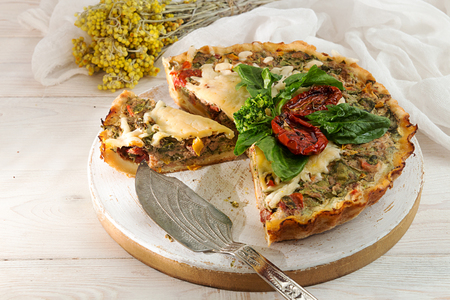 French opened pie quiche with tuna  chicken, broccoli, spinach, pepper, eggs, cheese and dried tomato on white wooden background.  Stock Photo